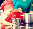cute little girl learning to cook with mother in kitchen