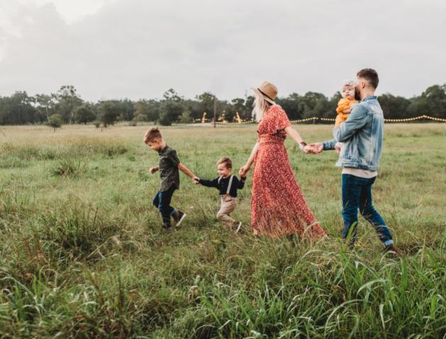 Famille de trois enfants qui marche dans un champ