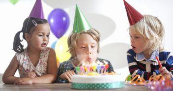 Enfant qui souffle ses bougies d'anniversaire avec ses amis