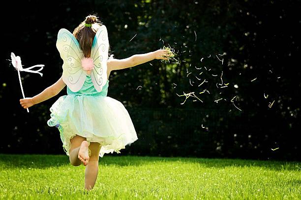 Petite fille qui court de dos dans l'herbe avec un déguisement de fée