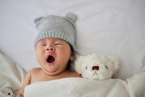 Bébé avec un bonnet gris avec oreilles en train de bailler dans son lit avec son nounours blanc