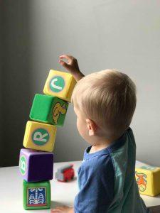 Bébé blond en train d'empiler des cubes en mousse pour jouer