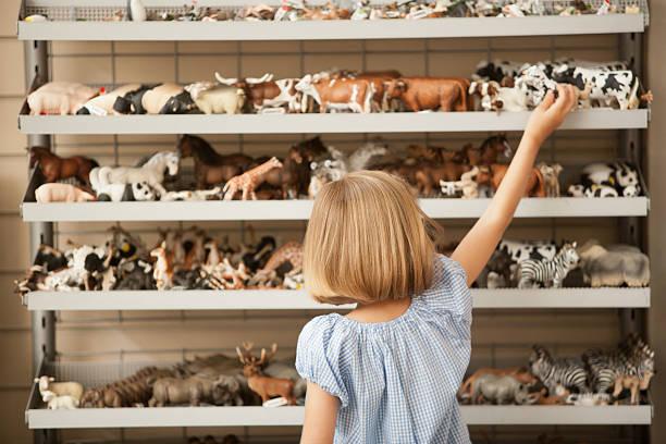 Petite fille de dos qui saisit un jouet sur une étagère