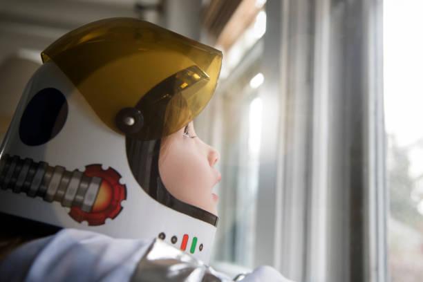 Petite fille dans un costume d'astronaute qui regarde par la fenêtre