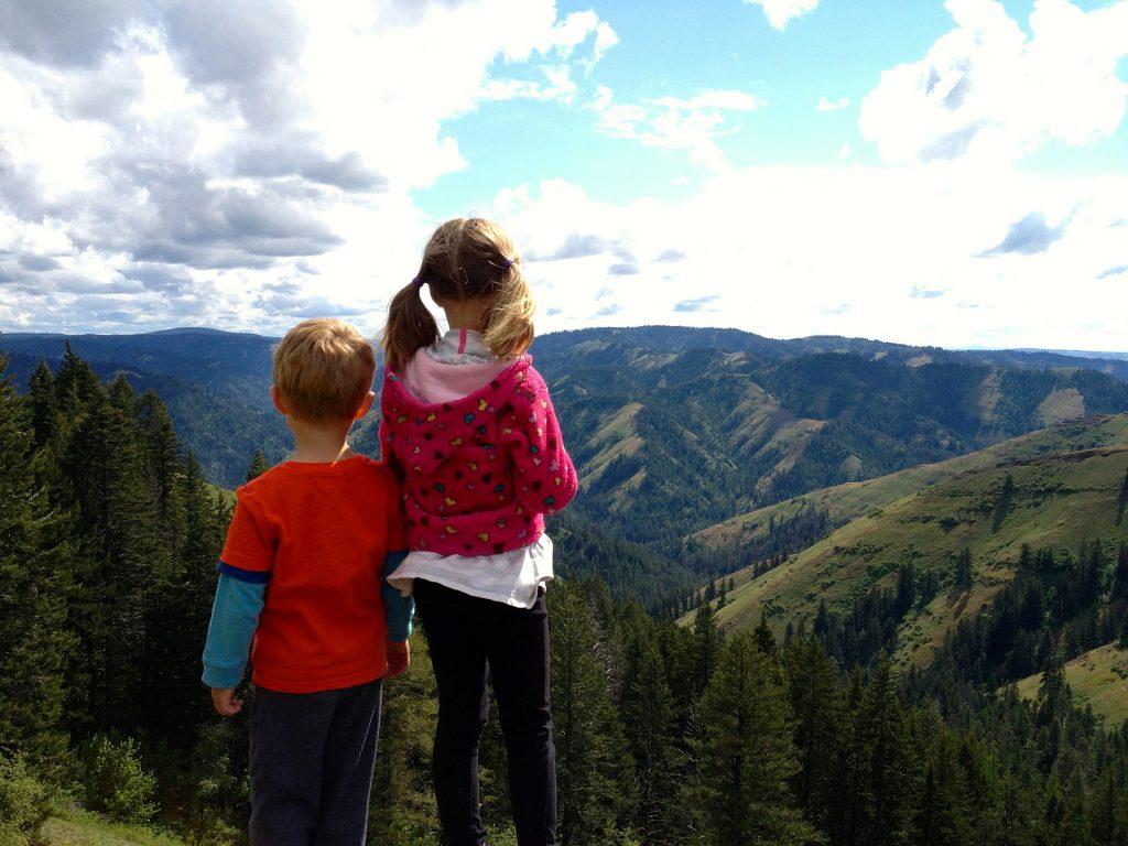 Deux enfants de dos regardent le paysage à la montagne
