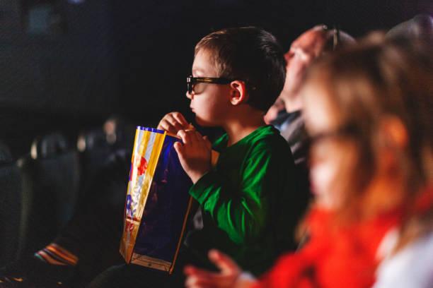 Petit garçon au cinéma, avec des lunettes 3D et un pot de popcorn