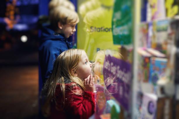 Petite fille qui colle son nez contre la vitrine d'un magasin de jouets
