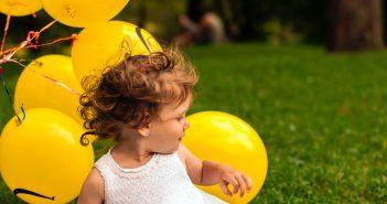 Petite fille en train de jouer dans l'herbe avec des ballons jaunes